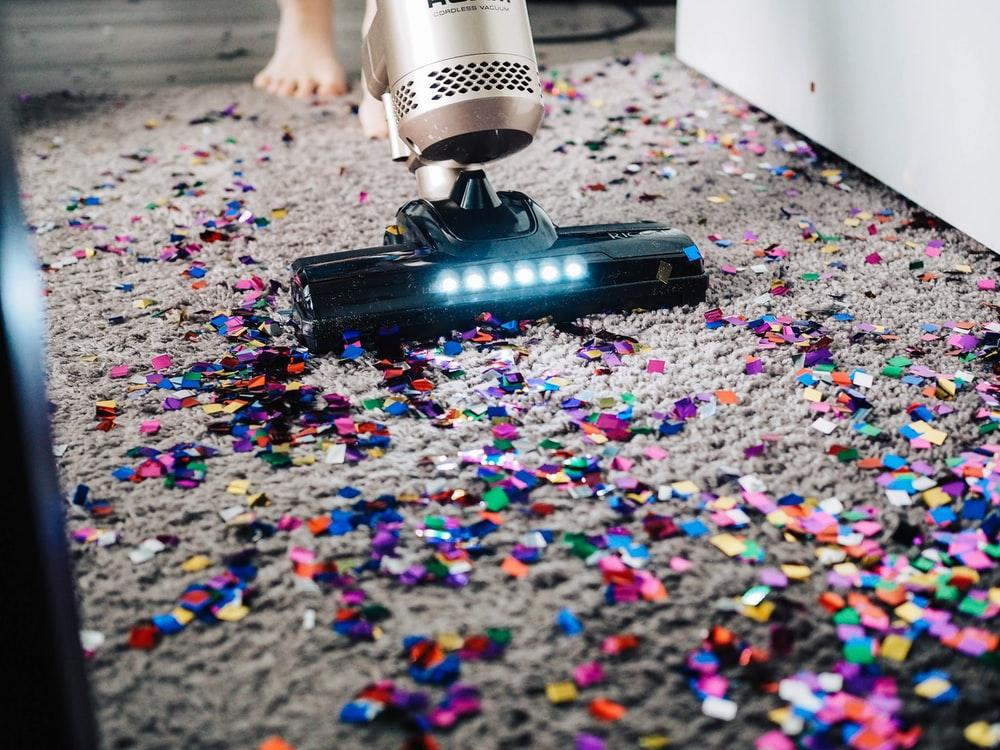 Vacuum cleaner being used to clean confetti from carpet